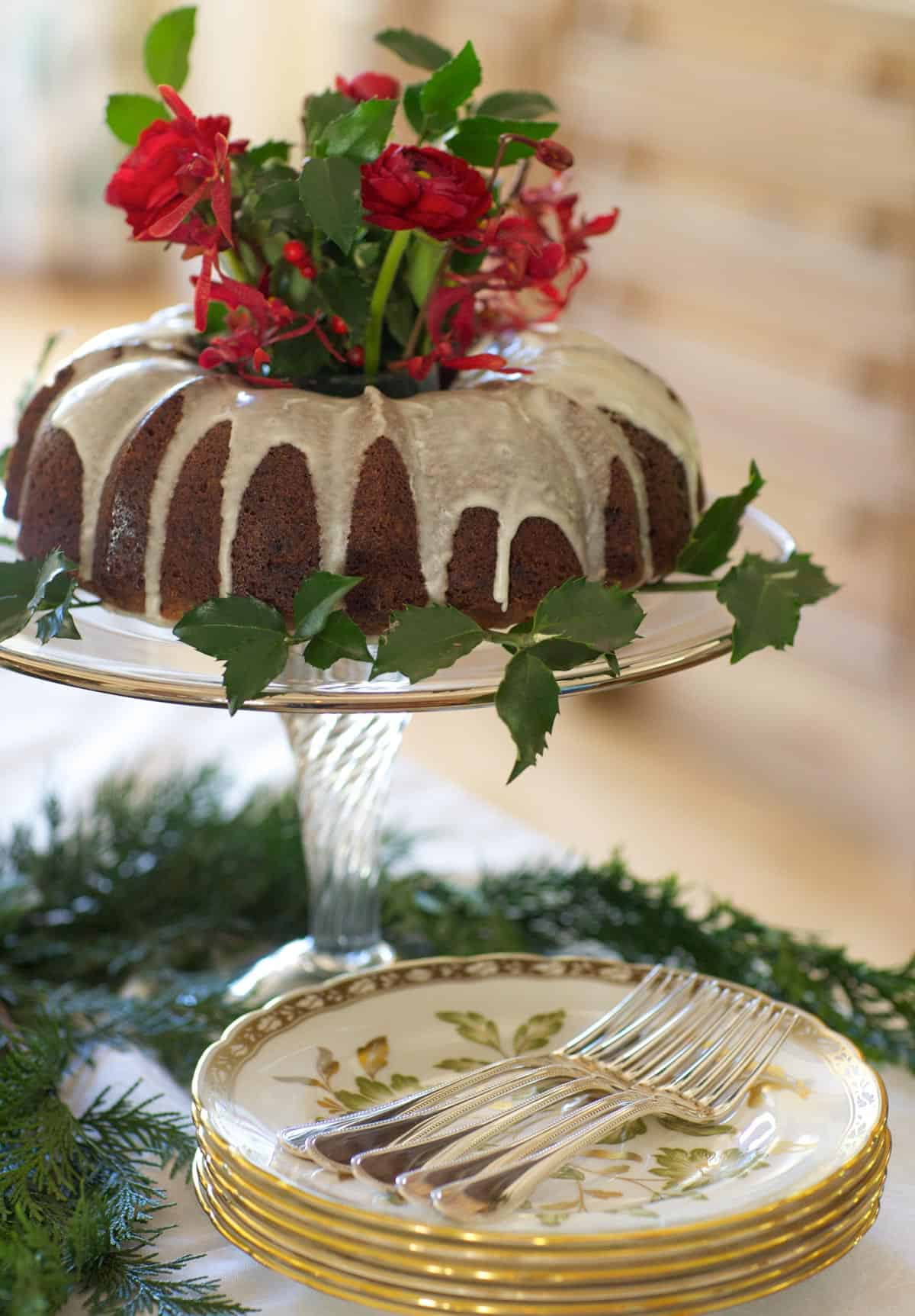 Bundt pan-shaped Apple Cake on a glass cake stand with flowers