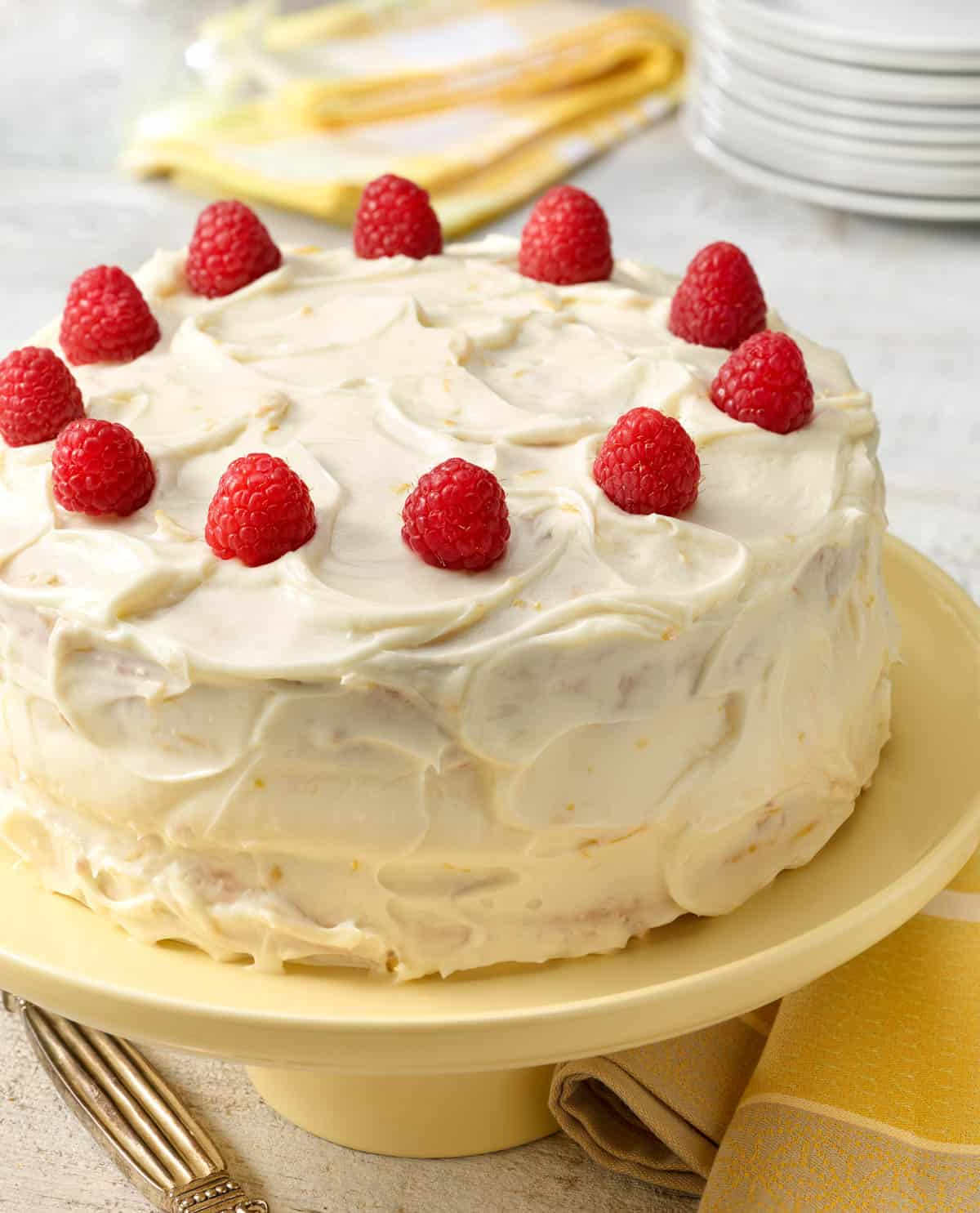 Banana Raspberry Cake with Lemon Frosting on a cake stand