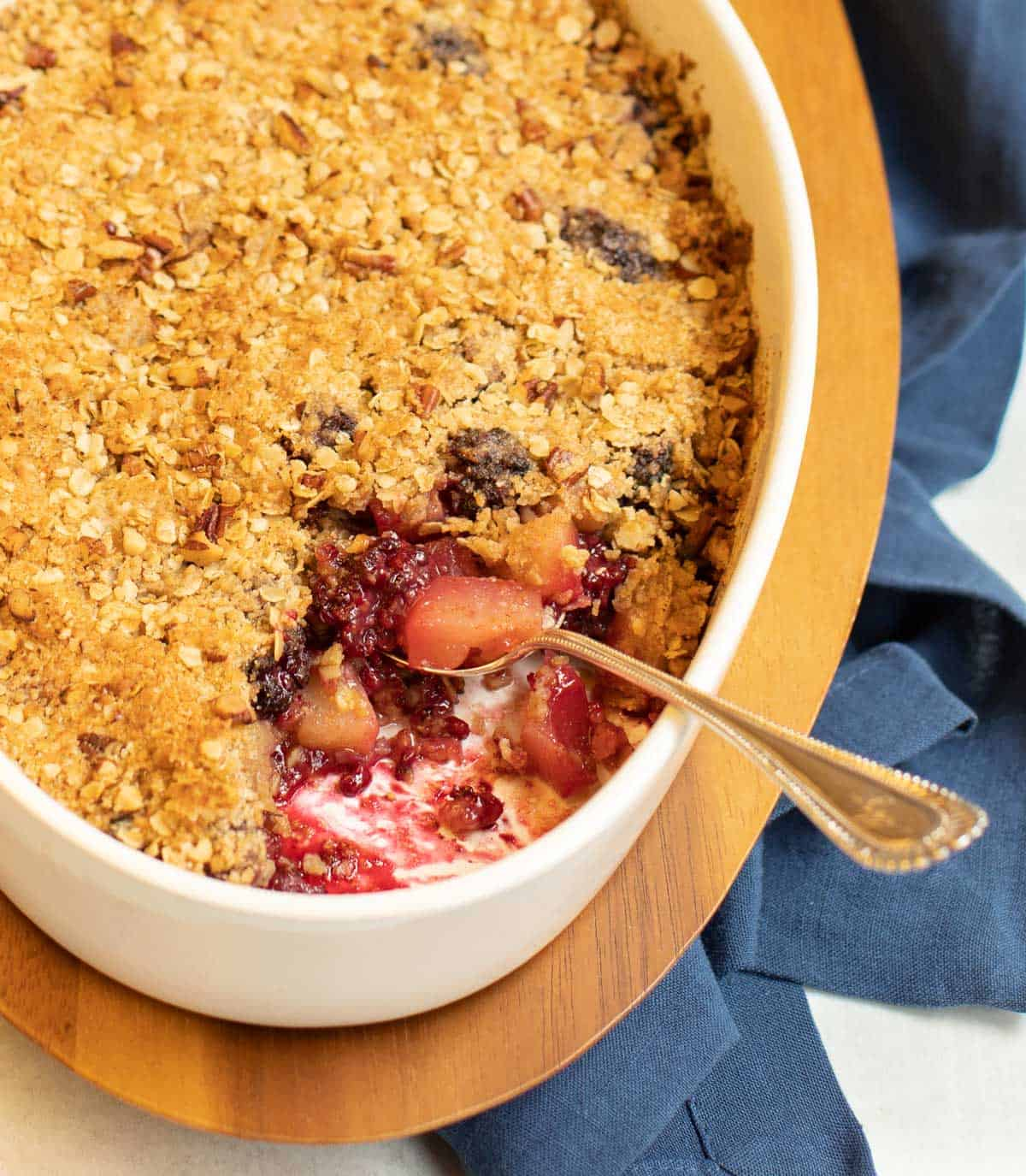 Blackberry Pear Crisp in a white oval dish with a scoop out of one corner