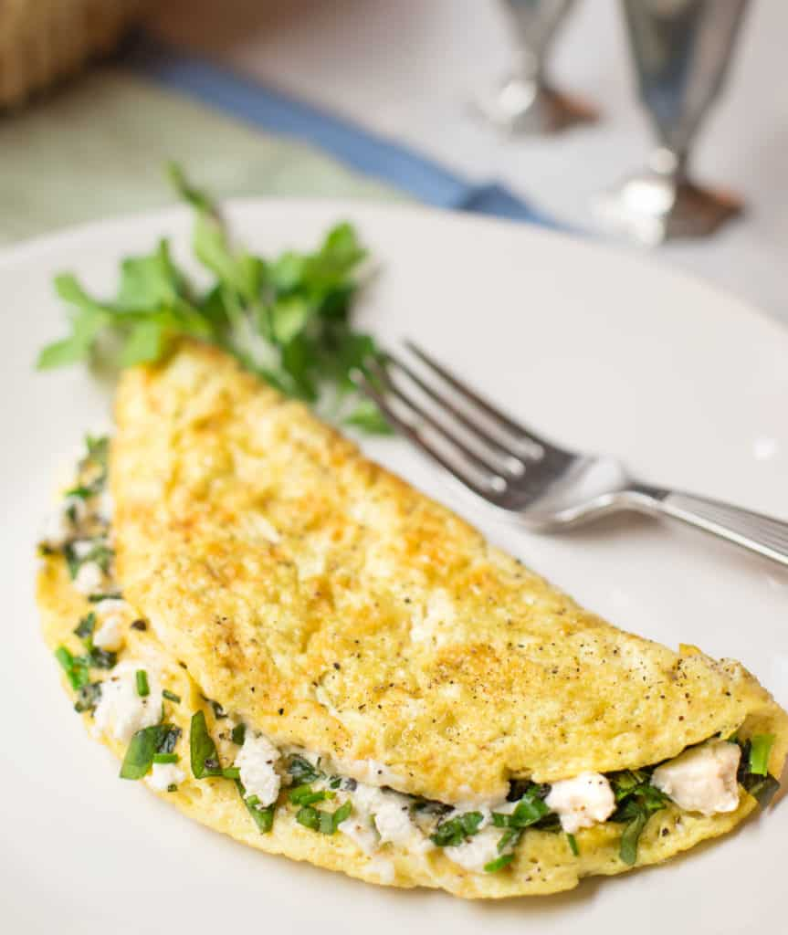 White plate with a Goat Cheese and Fresh Herb Omelet