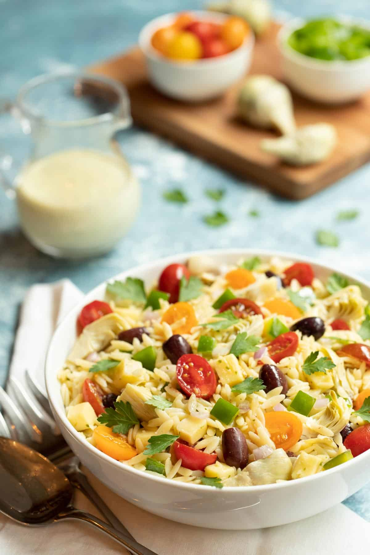 White bowl filled with Greek Orzo Salad with Lemon-Basil Tahini Dressing. Dressing is on the side