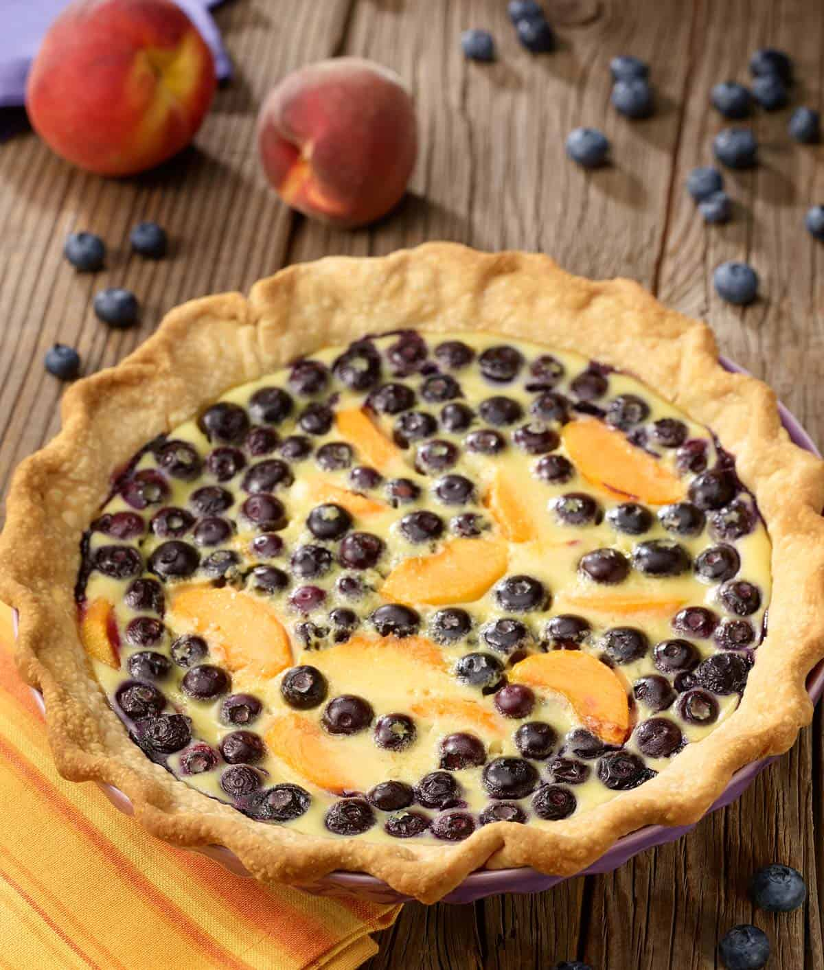 Blueberry peach custard pie with peaches and blueberries on the sdie