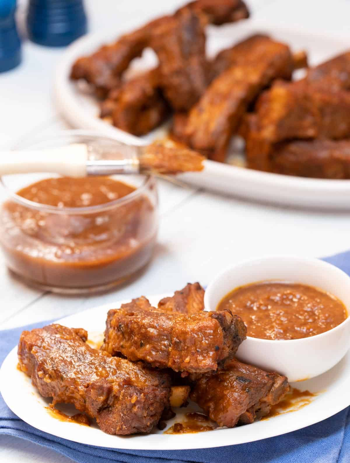 White dishes with Braised Baby Back Ribs with Zesty BBQ Sauce
