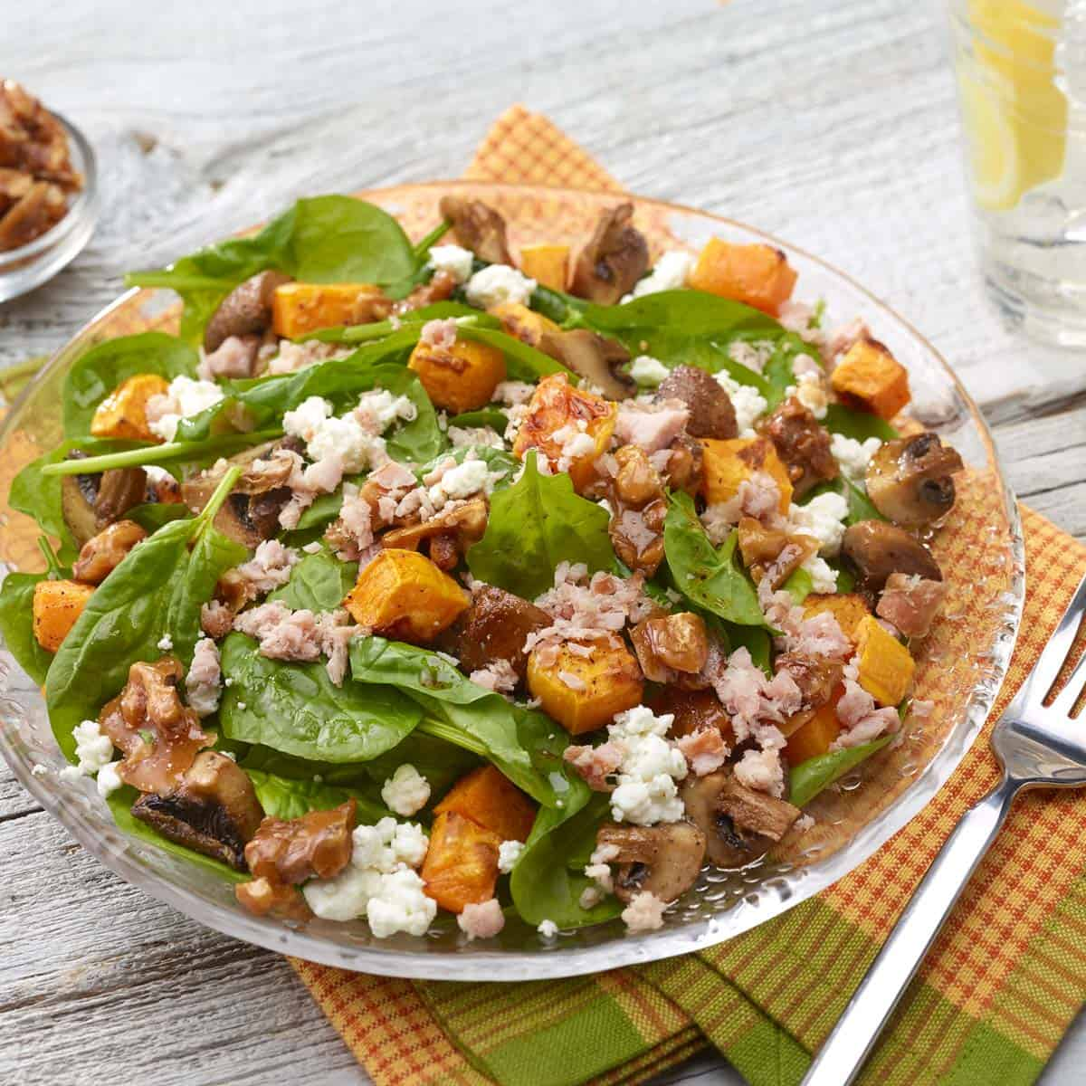 Roasted buttrnut squash and mushroom spinach salad in a glass bowl