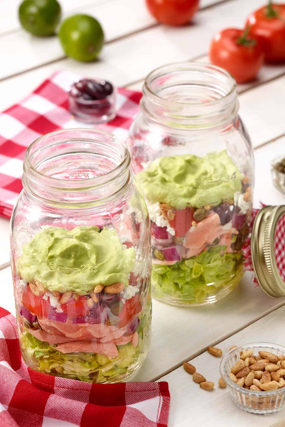 large mason jars filled with Layered Salmon Salad with Avocado Dressing