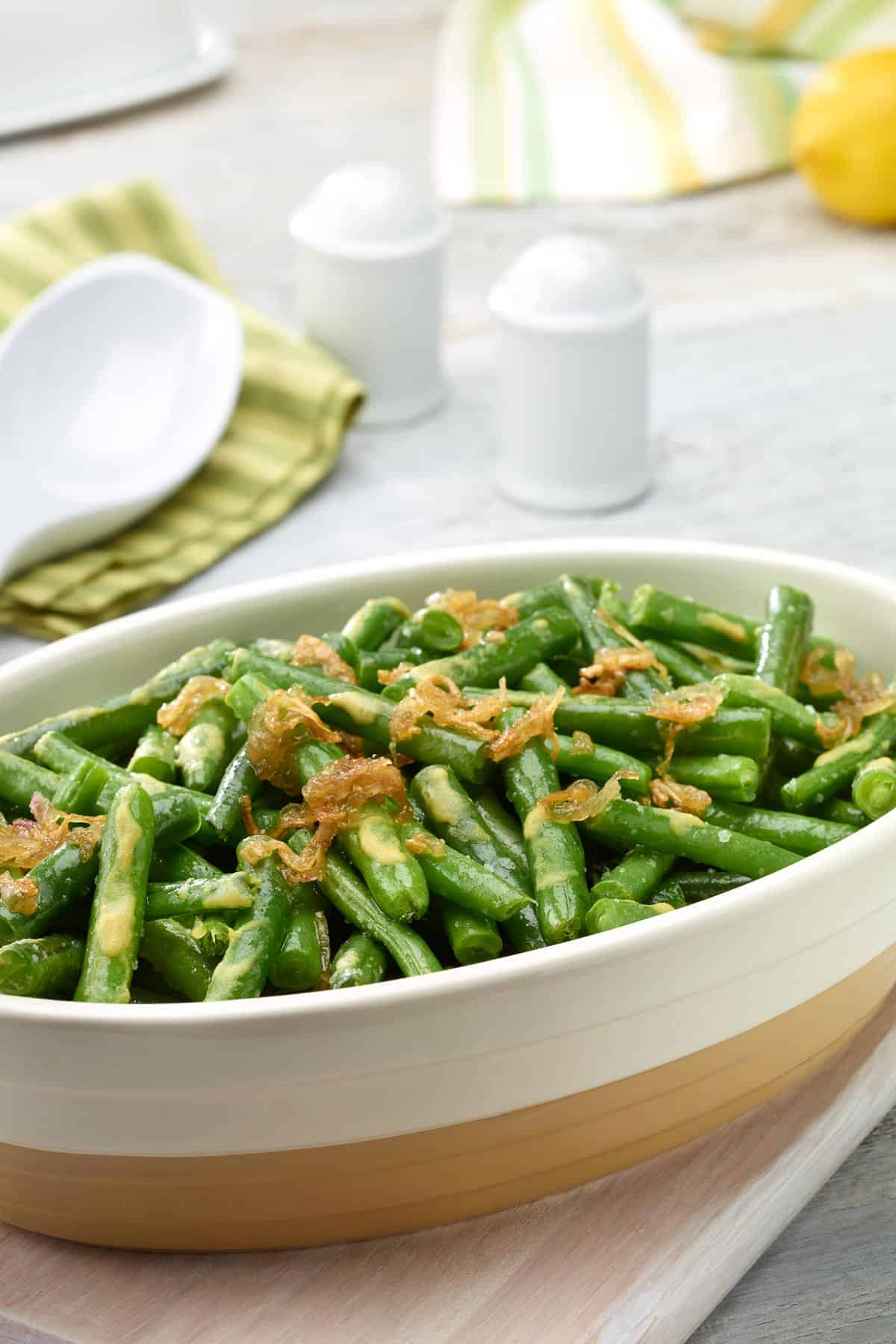Oval white dish filled with Lemon-Dijon Green Beans with Caramelized Shallots