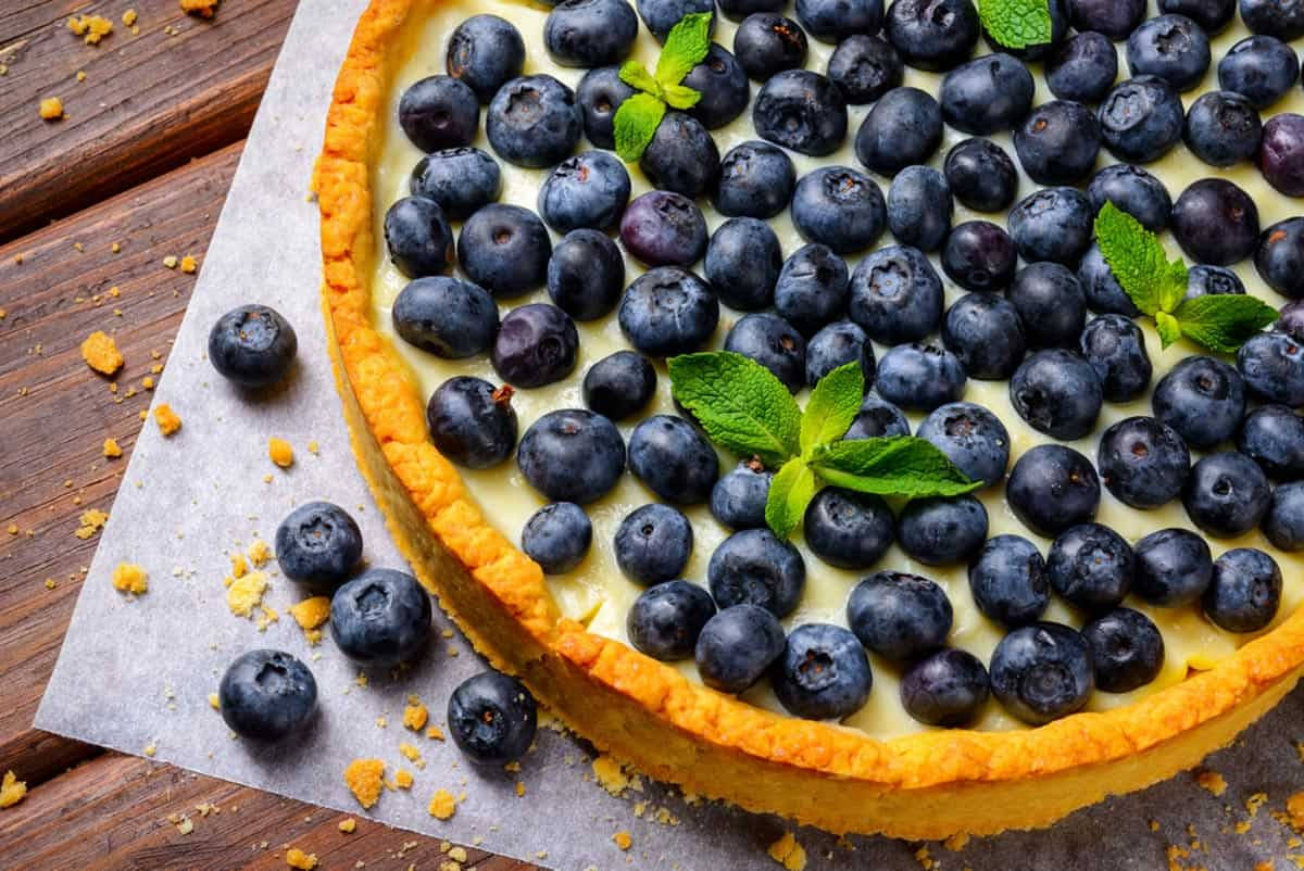 Gingersnap crusted tart filled with creamy lemony filing and topped with blueberries