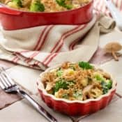 small red dish with broccoli,mushroom, spinach and cheese pasta with larger pot in the background