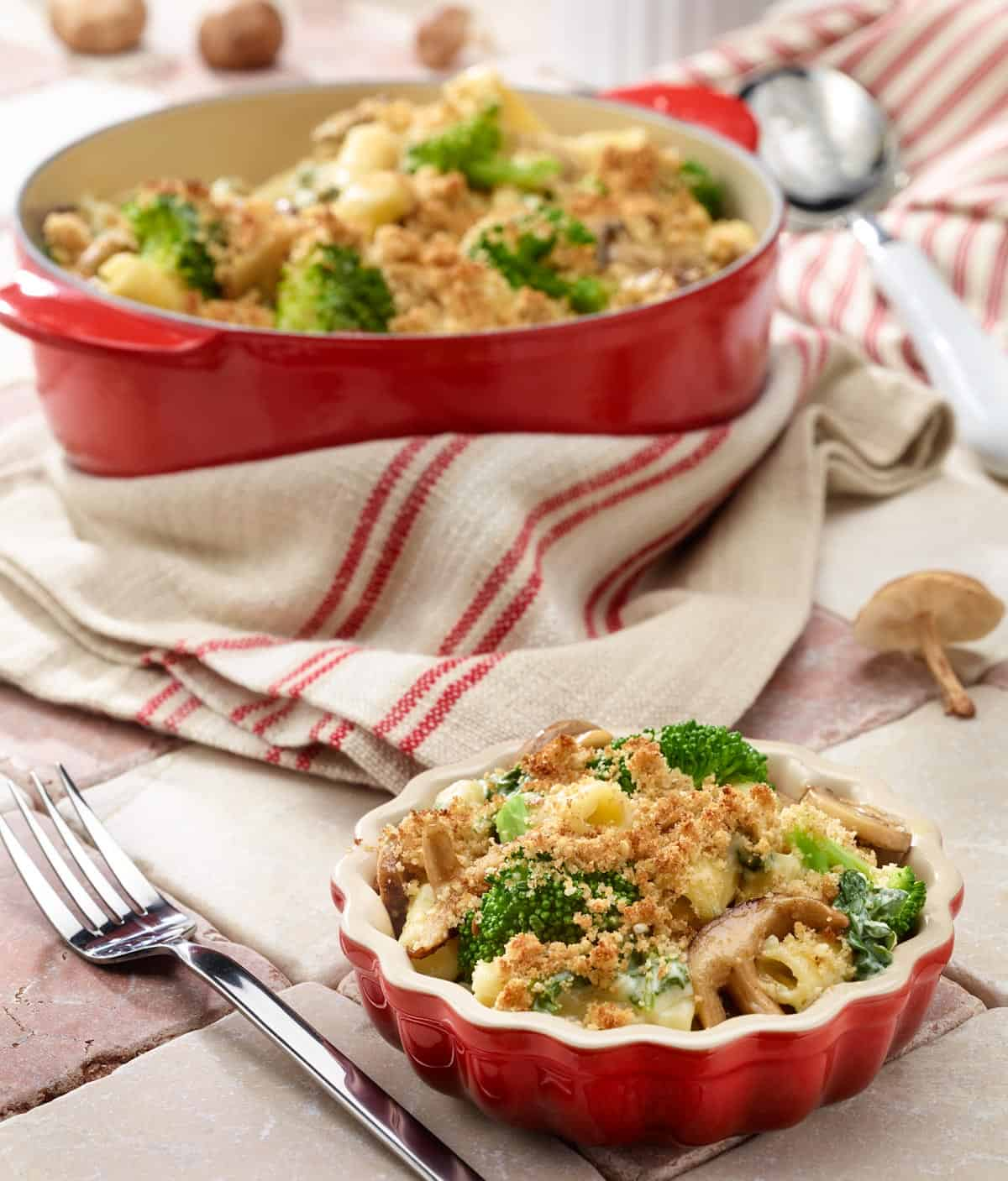 Small dish of broccoli, mushroom, spinach and cheese pasta with larger pan in background