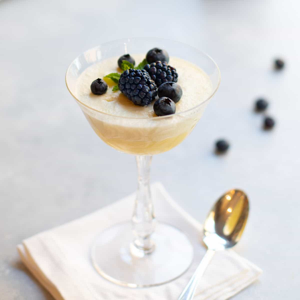 champagne coupe glass filled with Chilled Lemon Souffle and topped with fresh blackberries and blueberries