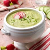Chilled cucumber leek vichyssoise soup garnished with sliced radishes