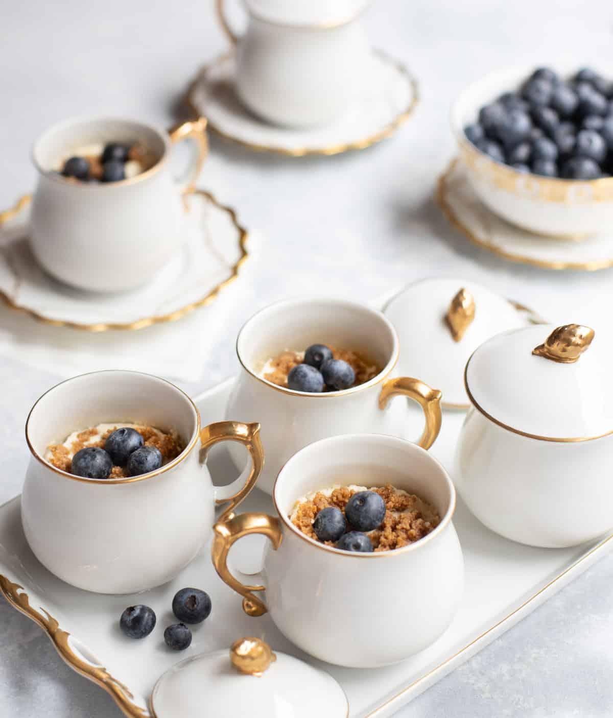 White pots de creme filled with Frozen Lemon Velvet, topped with fresh blueberries