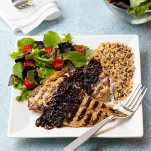 Grilled chicken breasts topped with caramelized red onion
