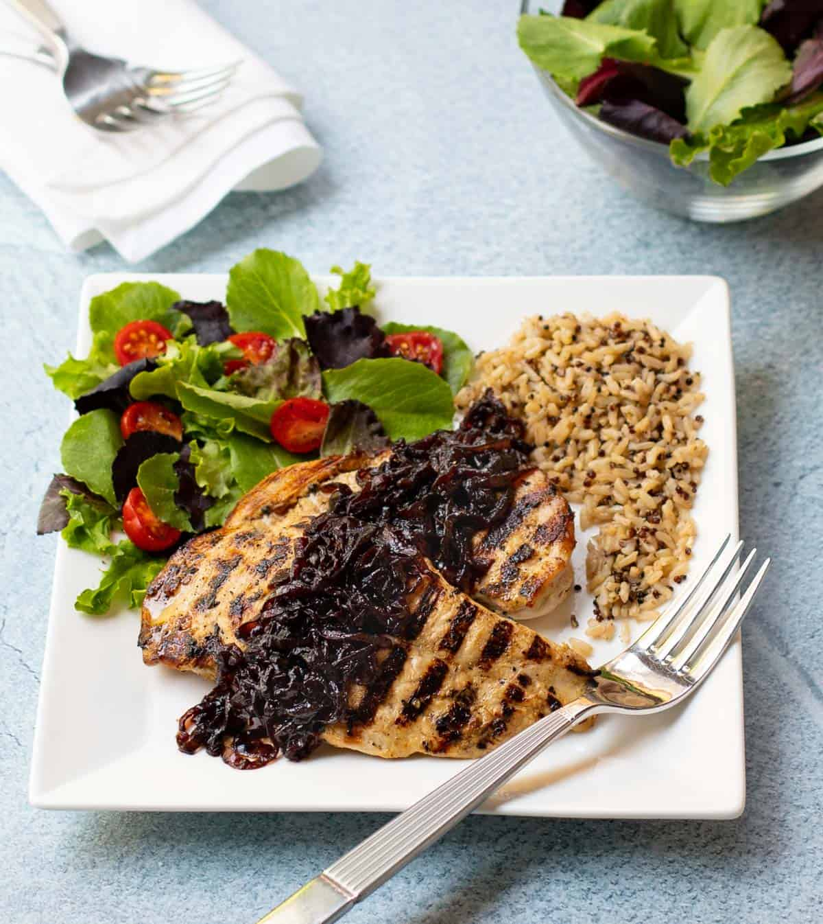 Grilled chicken breasts with caramelized red onion, quinoa and brown rice, and tossed salad