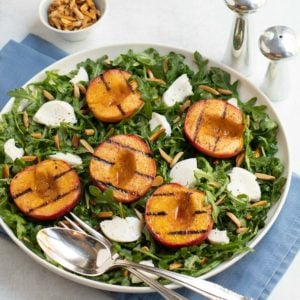 Grilled peach halves and sliced Mozzarella cheese on top of baby arugula salad