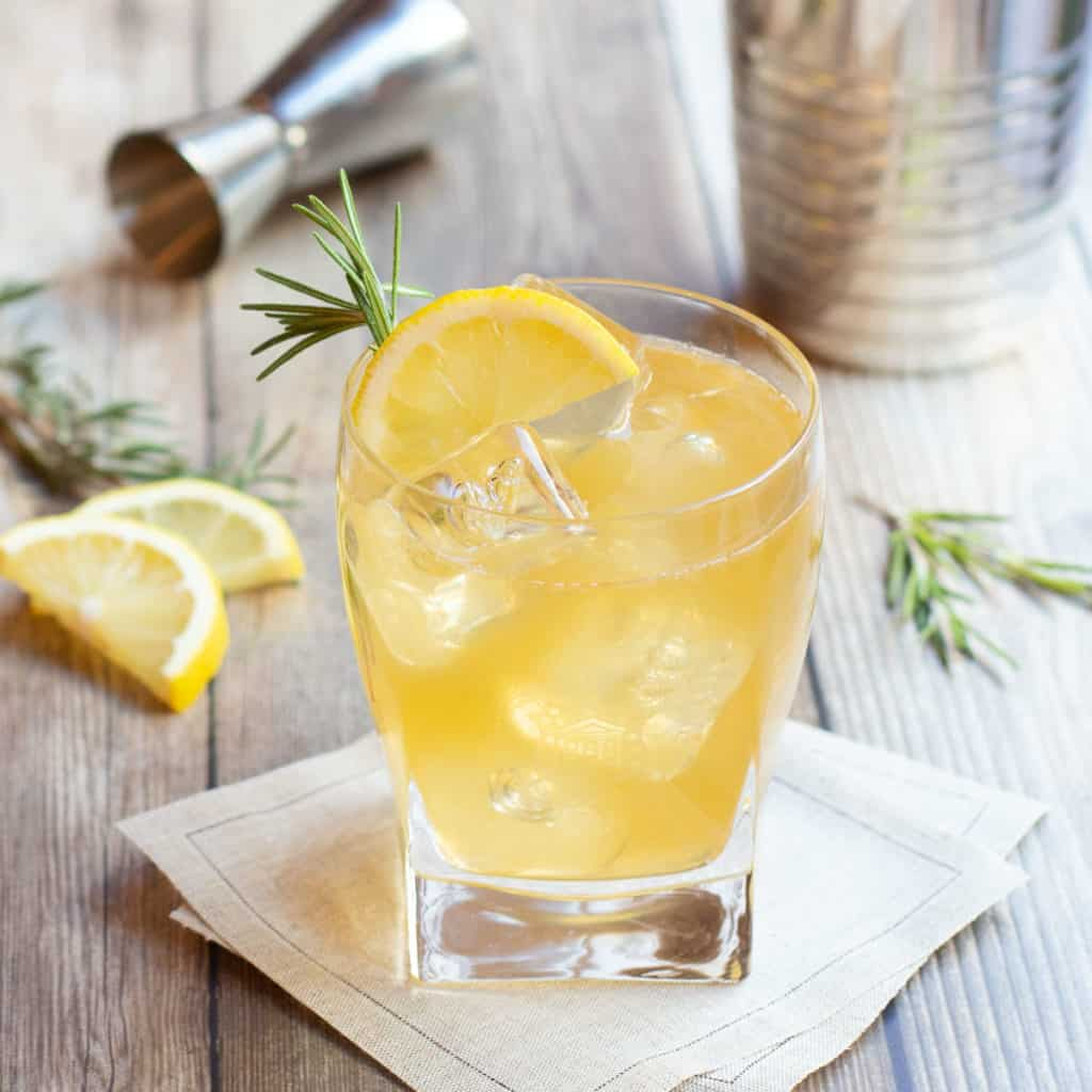 lemon ginger bourbon cocktail over ice in a glass, garnished with a lemon slice