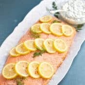 Poached salmon garnished with lemon slice and dill, with a side of cucumber dill sauce