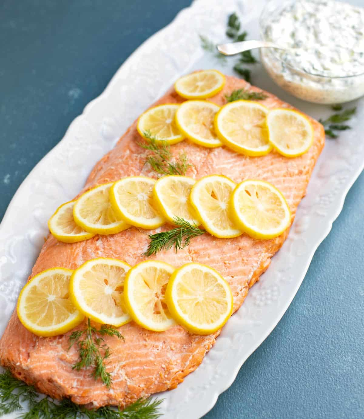 Oven poached salmon garnished with lemon slices and dill, with a side of cucumber dill sauce