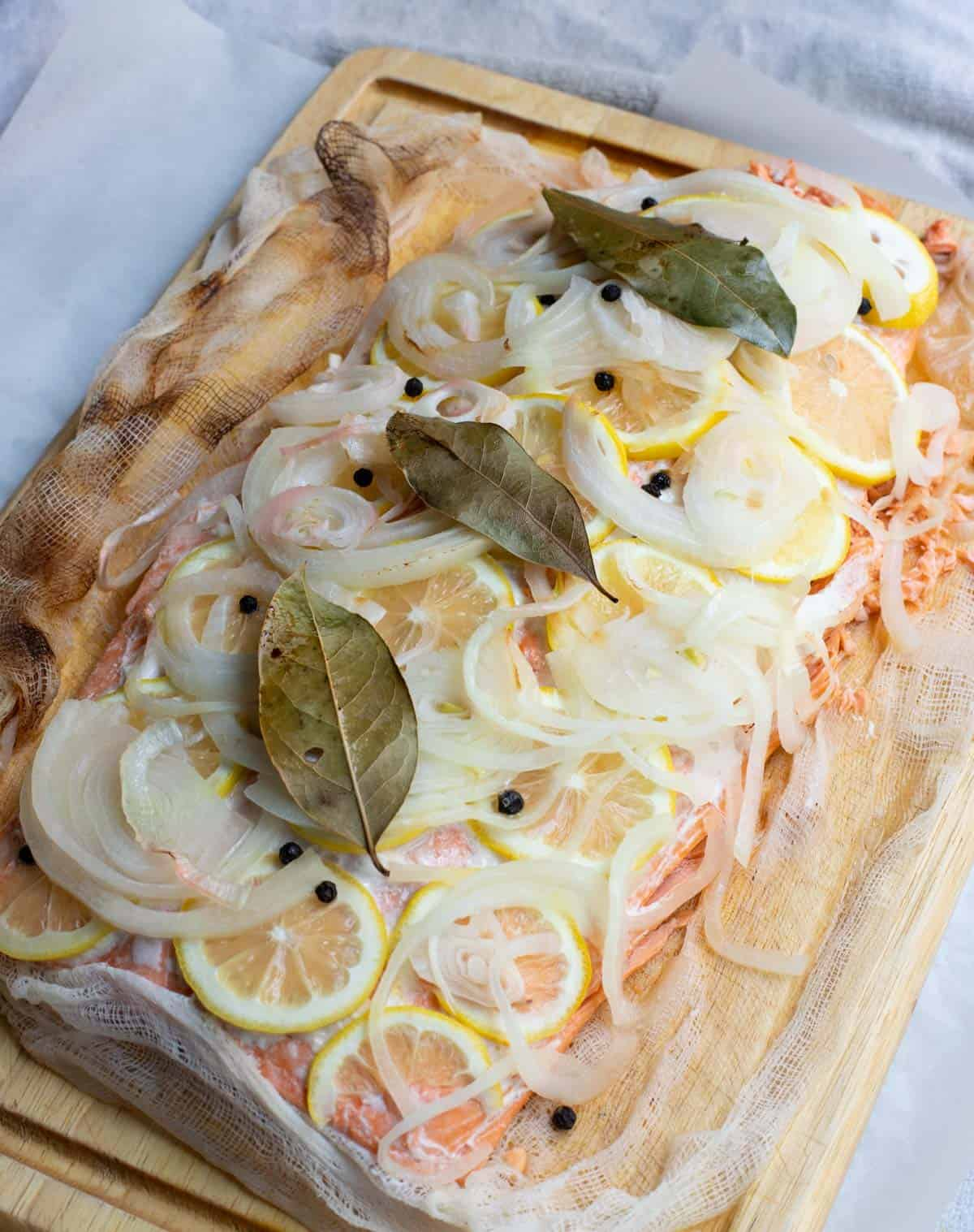 Poached salmon fillet topped with lemon, onion, peppercorns and bay leaves