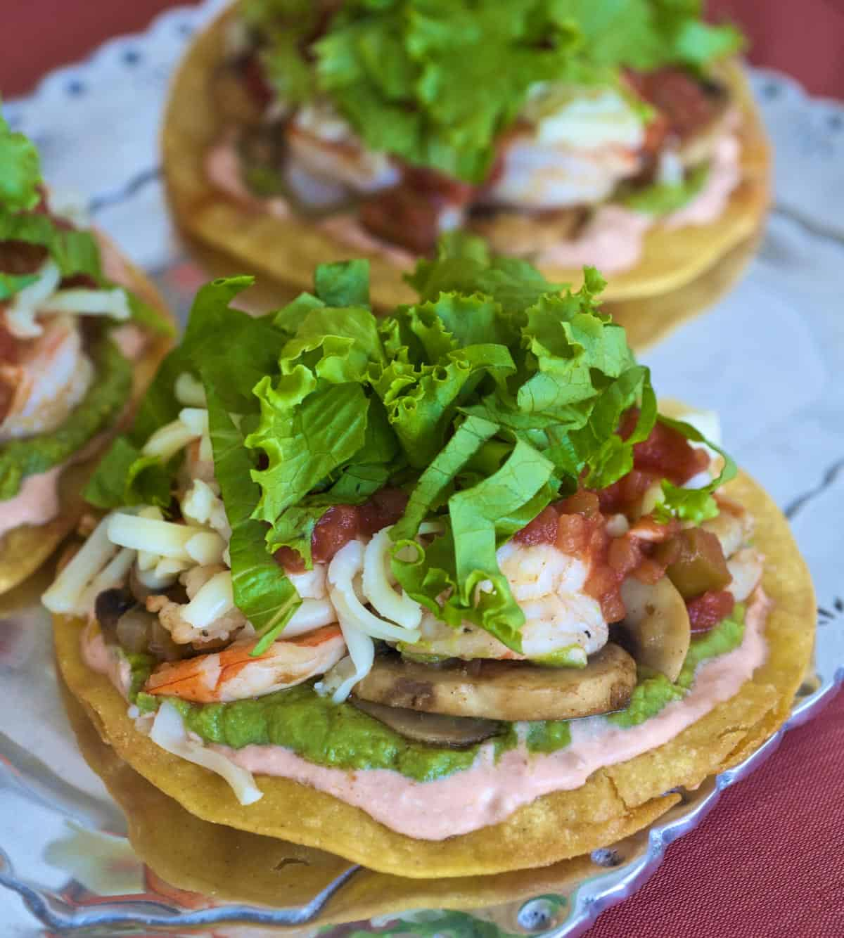 Sauteed shrimp and vegetables layered atop crispy corn tortillas with shredded cheese and lettuce