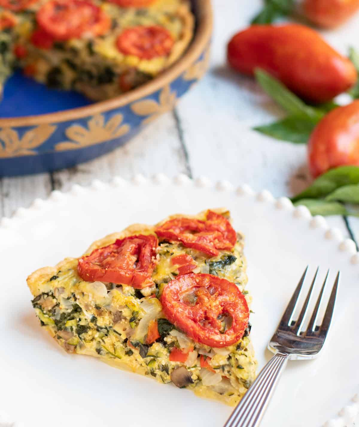 Slice of Mushroom, Spinach, Tomato and Zucchini Pie on a white plate