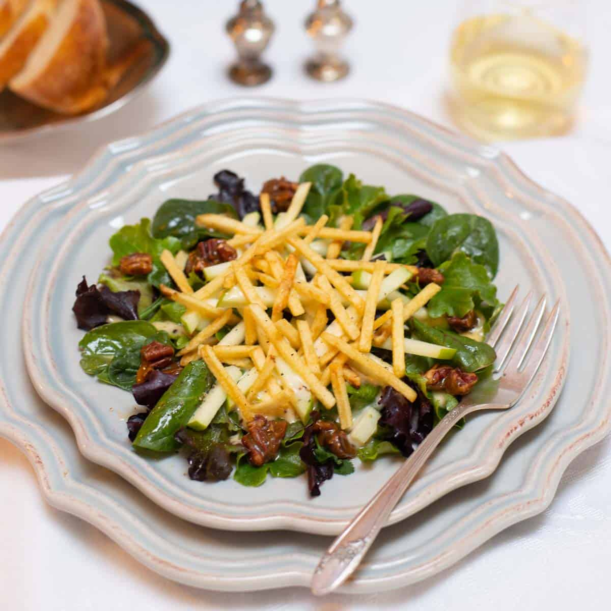 Individual plate filled with a serving of Apple and Mixed Greens Salad with Apple-Truffle Vinaigrette