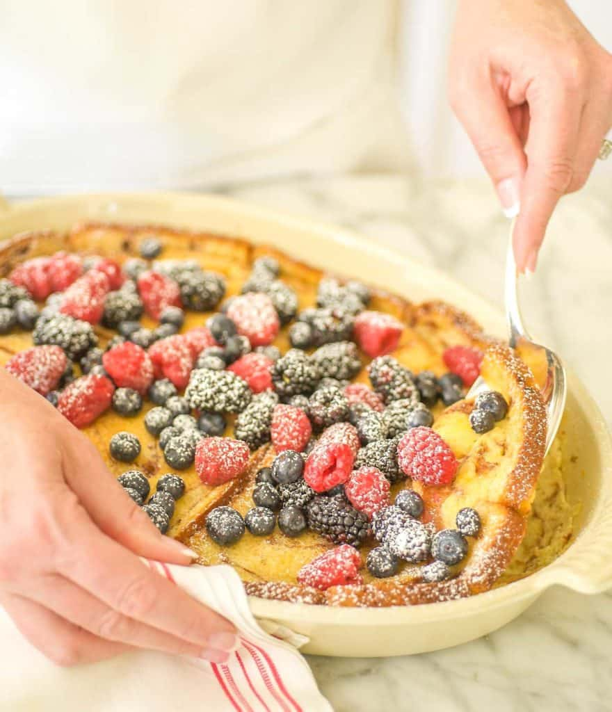 Oval baking dish filled with Baked Cinnamon French Toast, topped with berries and a spoon dishing out one serving