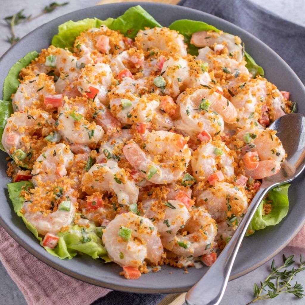 Dark blue plate holding Shrimp Salad with Lime Herb Dressing, with a serving spoon on the side