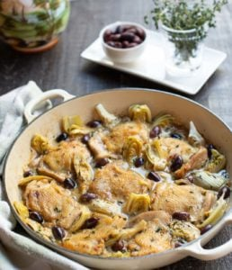 braised chicken thighs with olives and artichoke hearts in a shallow Dutch oven