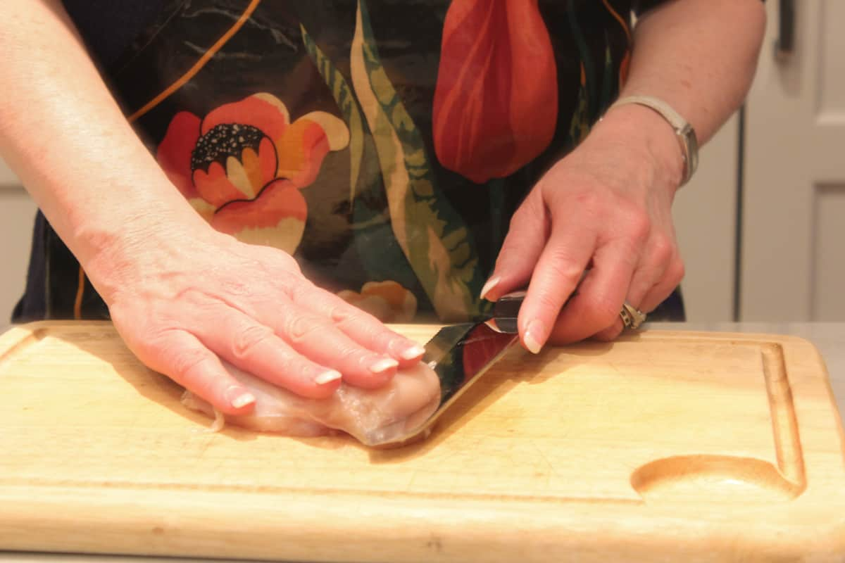 Step one of butterflying a chicken breast - slicing from the side with hand on top