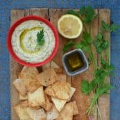 bowl of Cannellini Dip with Truffle Oil on a board with pita chips