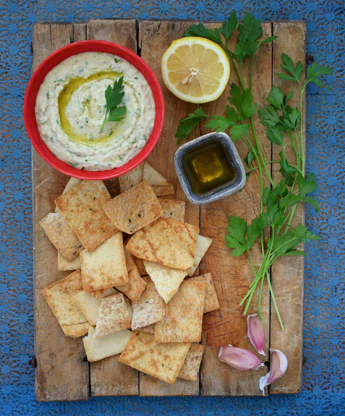 Bowl of Cannellini Bean Dip with Truffle OIl on a wooden board with pita chips