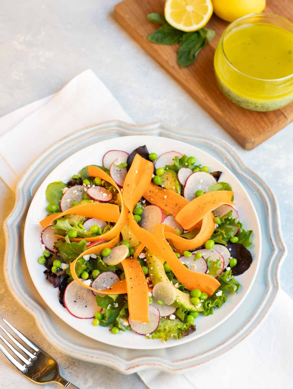 Shaved carrots, radishes and sweat peas arranged with lettuces and avocado and lemon basil vinaigrette