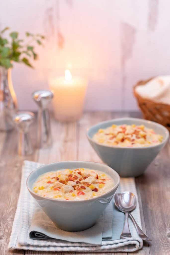 two bowls filled with Corn and Chicken Chowder with a basket of bread and a candle in the background