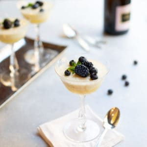 Champagne coupe glasses filled with Chilled Lemon Souffles, topped with blackberries and blueberries