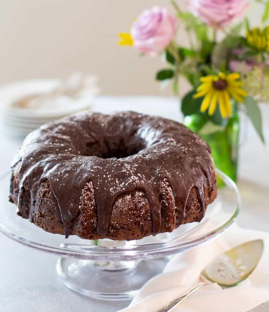 triple chocolate zucchini cake on a glass cake stand