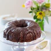 Triple Chocolate Zucchini Cake on glass cake platter