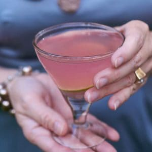 hands holding a Cosmopolitan Martini