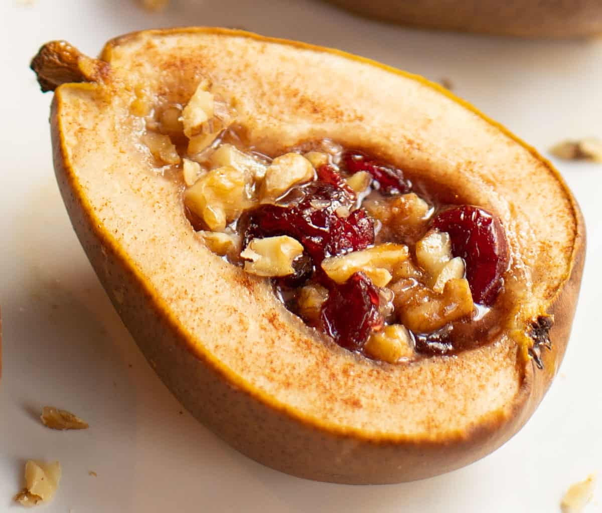 close up shot of a baked half pear stuffed with dried cranberries and chopped walnuts
