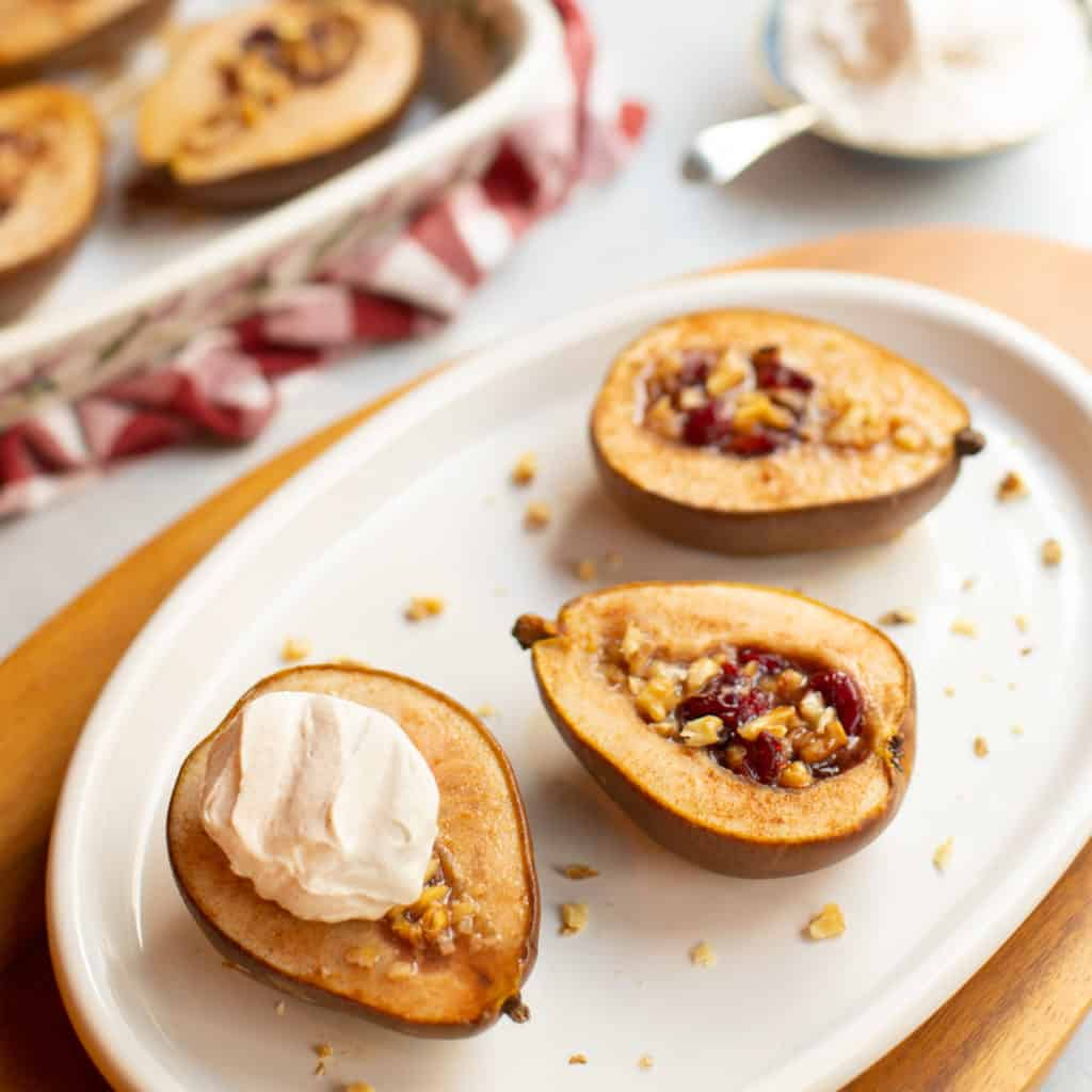 white oval plate with halved pears stuffed with cranberries and walnuts, topped with cinnamon whipped cream