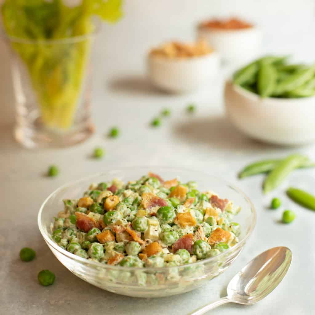 glass bowl filled with Curried Pea Salad with Bacon and Cashews