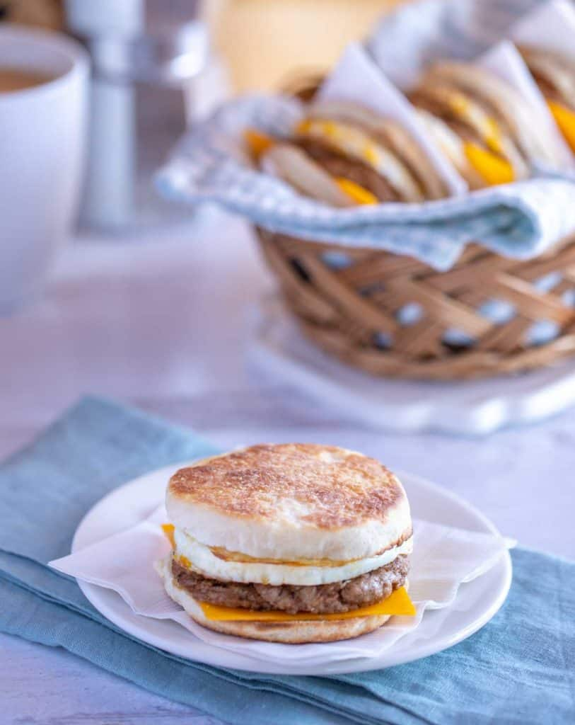 White plate showing a quick and easy Breakfast Sandwich with Egg; basket of sandwiches in the background