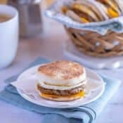 white plate showing an Egg Breakfast Sandwich, with basket of sandwiches and coffee in the background