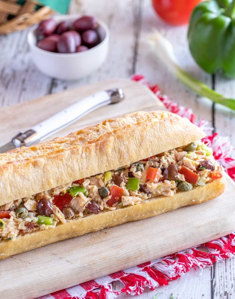 Cutting board holding Pan Bagnat - a french baguette stuffed with tuna nicoise filling.