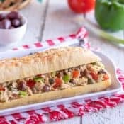 white platter holding a Pan Bagnat - crusty french baguette fiiled with Tuna Nicoise