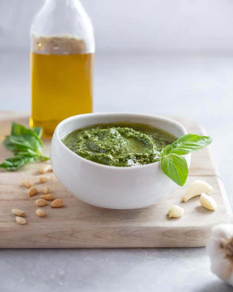 White bowl filled with Pesto Genovese, sitting on a cutting board with a bottle of olive oil in the background