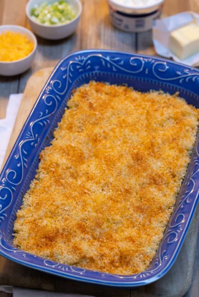 Blue baking dish filled with Golden Potatoes (Twice Baked Potato Casserole)