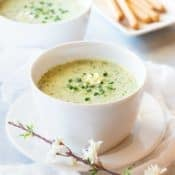 Bowl showing one serving of Pureed Green Pea Soup, with breadsticks in the background