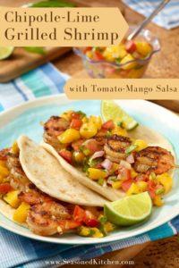 light blue plate holding 2 Chipotle Lime Shrimp Tacos with Tomato Mango Salsa