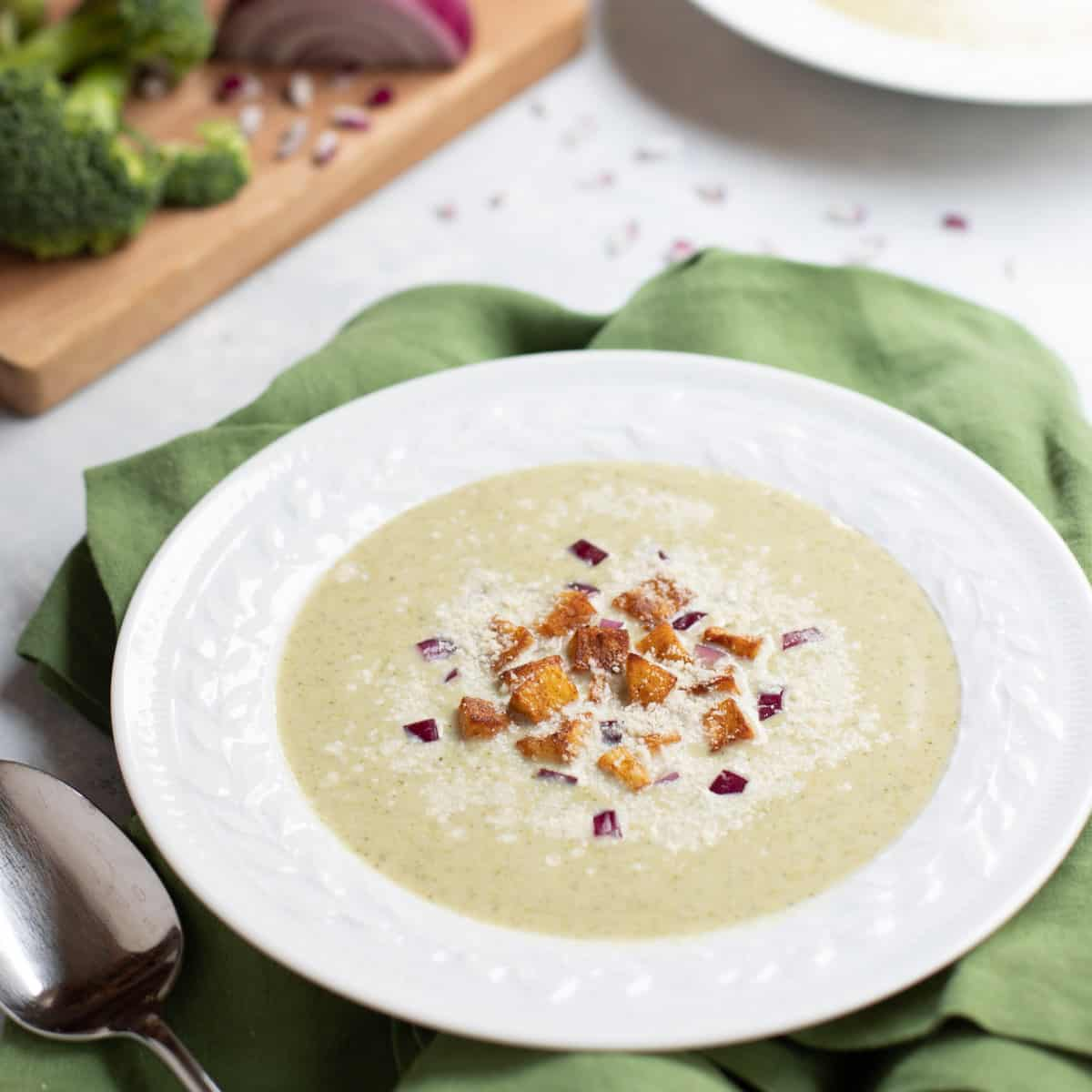 White bowl with Healthy Broccoli Soup topped with Potato Croutons, red onion and Parmesan